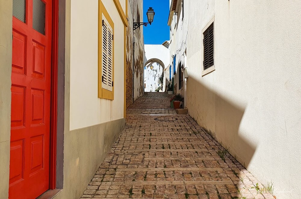 Narrow cobblestoned street between cute houses leading to a white arch