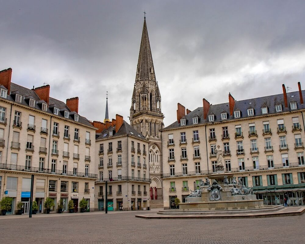 Royal square with fountain and church tower in Nantes city in France